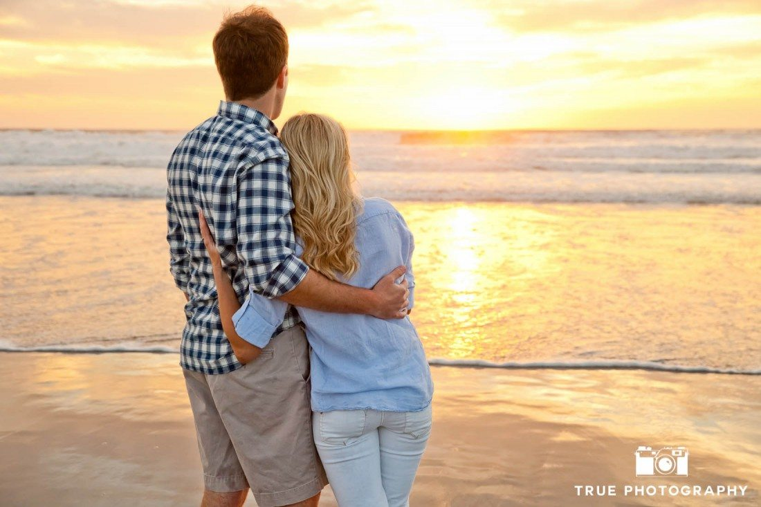 Engagement photo shoot of Mission Beach couple looking at waves