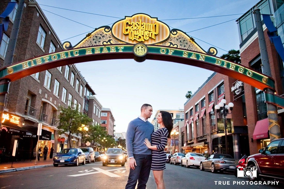engaged couple standing underneath Gaslamp sign San Diego