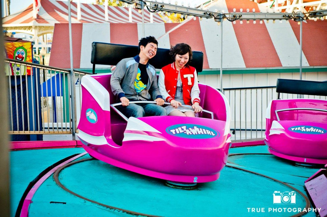 Engagement photo shoot of Mission Beach couple riding on purple carnival ride