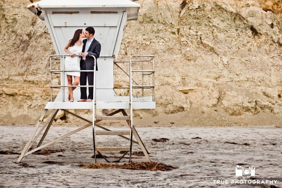 Engagement shoot of Del Mar Beach couple standing on lifeguard station