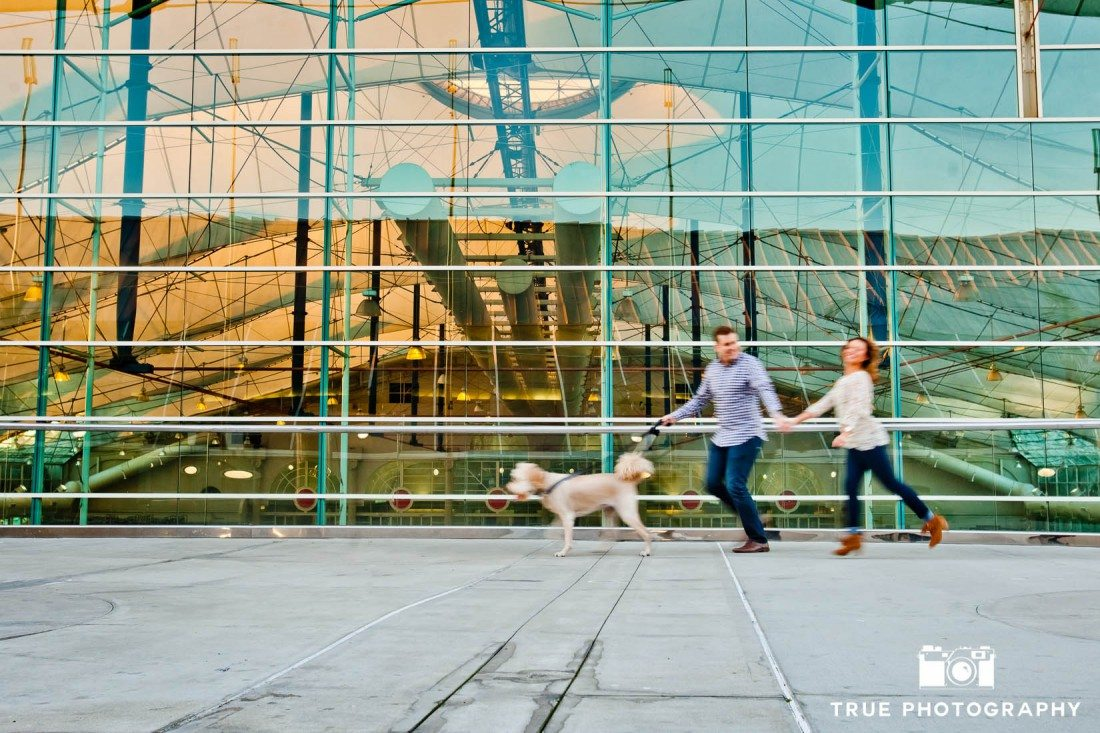 engaged couple chasing their dog at downtown San Diego engagement photo shoot