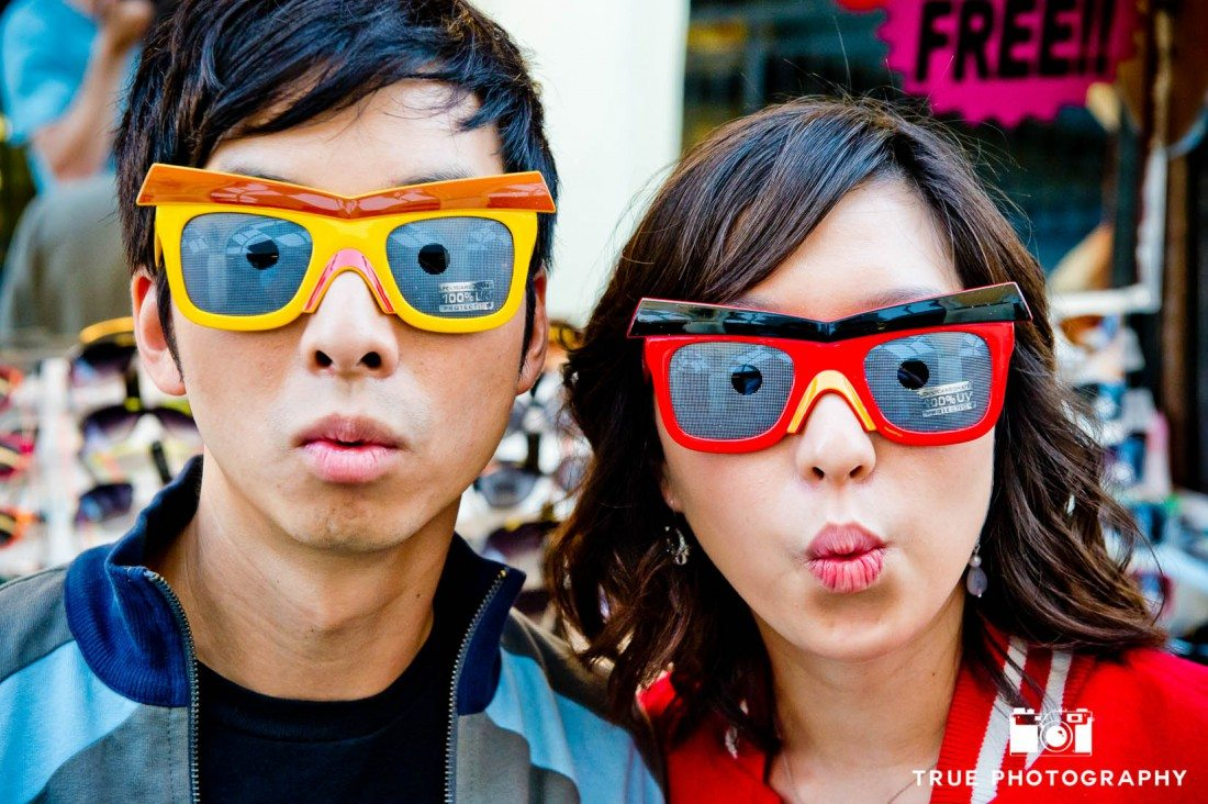 Engagement photo shoot of Mission Beach couple wearing silly sunglasses