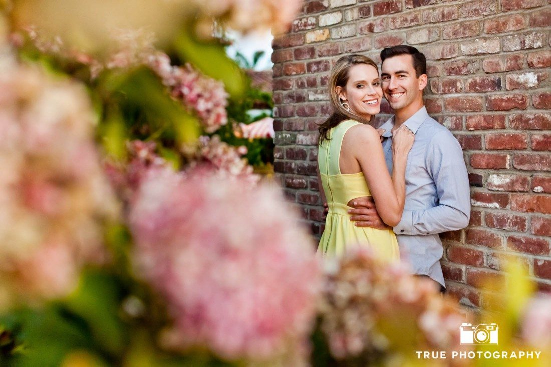 Old Town engagement shoot of couple  near brick wall with flowers
