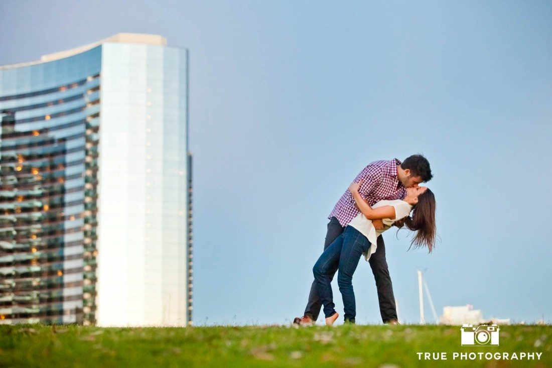 couple kissing on grass downtown San Diego engagement photo shoot