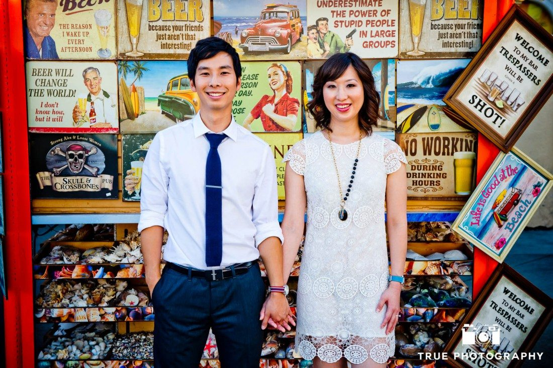 Engagement photo shoot of Mission Beach couple standing against t-shirt wall