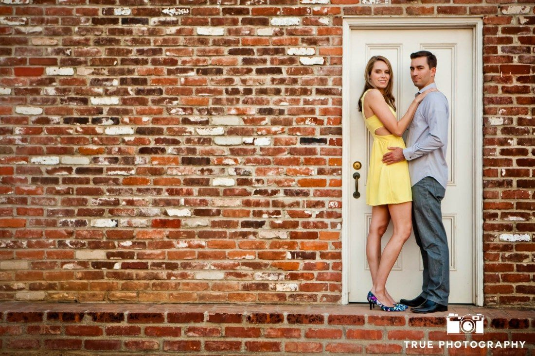 Old Town engagement shoot of couple standing with brick wall and white door