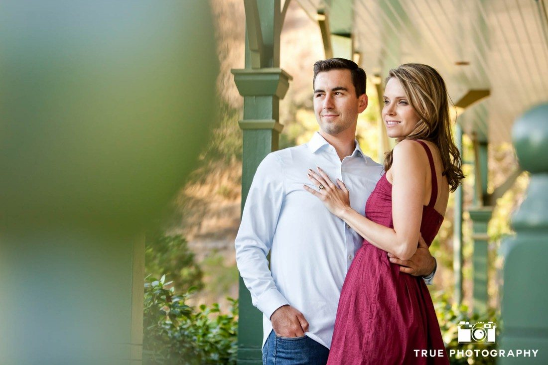 Old Town engagement shoot of couple standing against green post