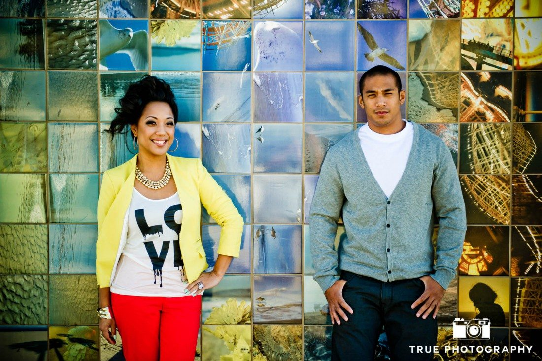 Engagement photo shoot of Mission Beach couplestanding against tiled background