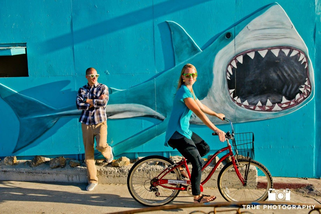 engagement photo shoot of Pacific Beach couple in front of shark picture