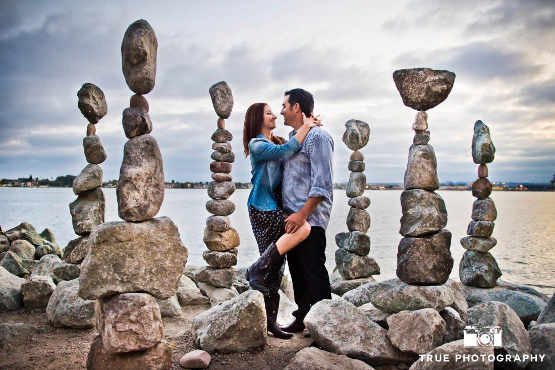couple standing near rocks at Seaport Village Engagement Photo Shoot