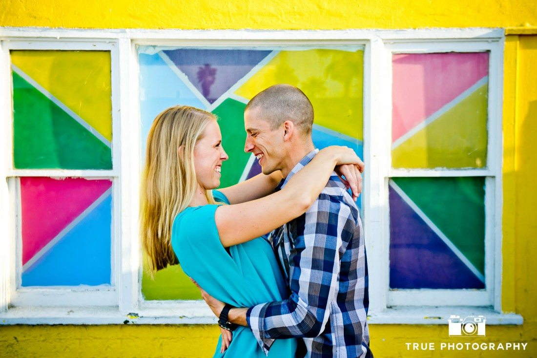 Engagement photo shoot of Pacific Beach couple with colorful mosaic background