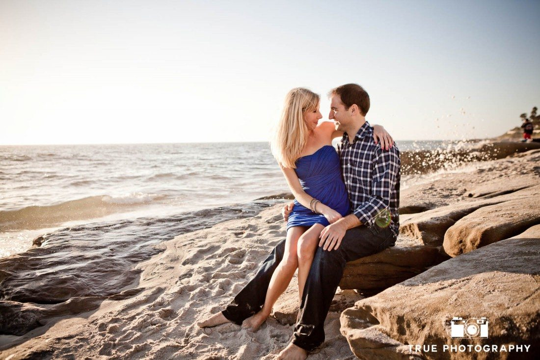 Windansea engagement photo shoot with couple sitting on sand