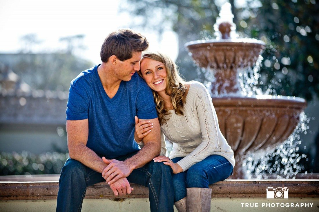 Engagement photo shoot of USD Campus couple sitting in front of fountain