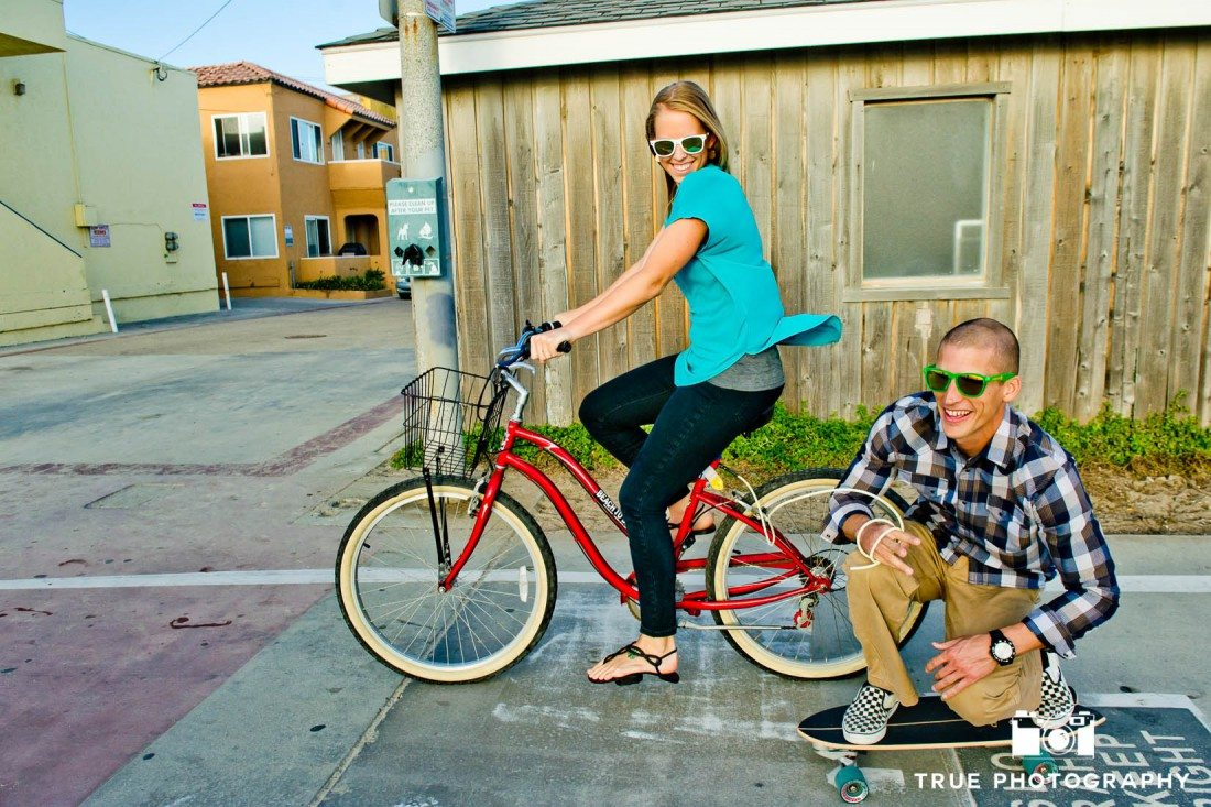 engagement photo shoot of Pacific Beach couple riding bike and skateboard
