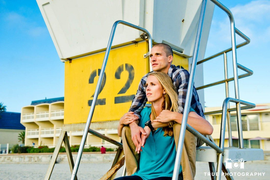 engagement photo shoot of Pacific Beach couple sitting on pier 22