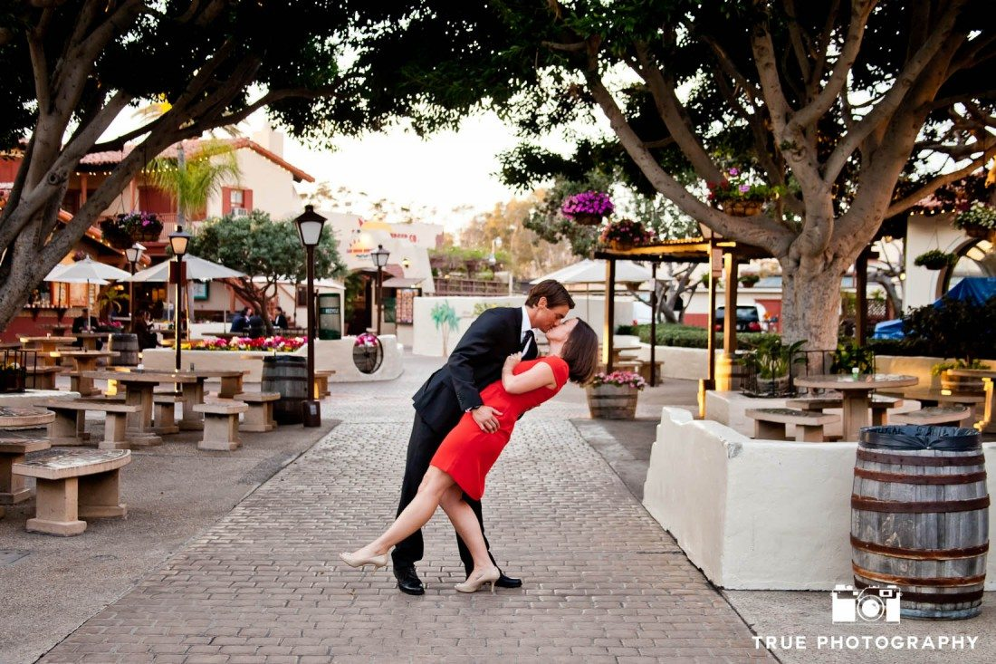 engaged couple kissing in Seaport Village