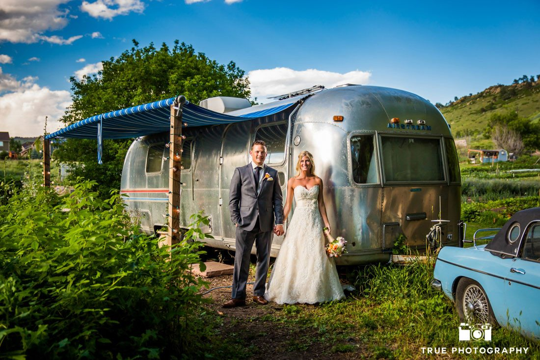 bride and groom in front of airstream trailer