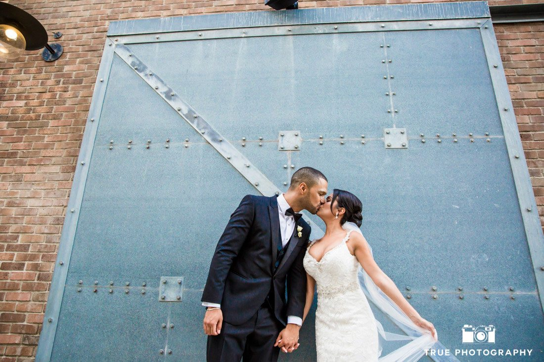 bride and groom kissing in front of blue door