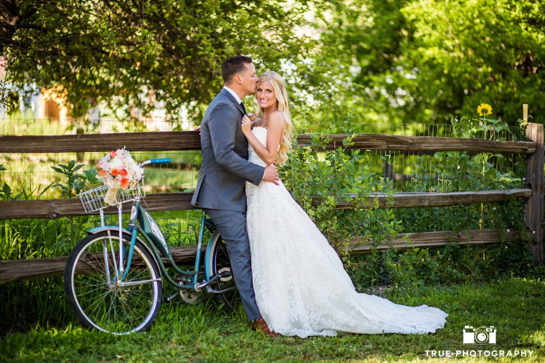 bride and groom leaning against bicycle