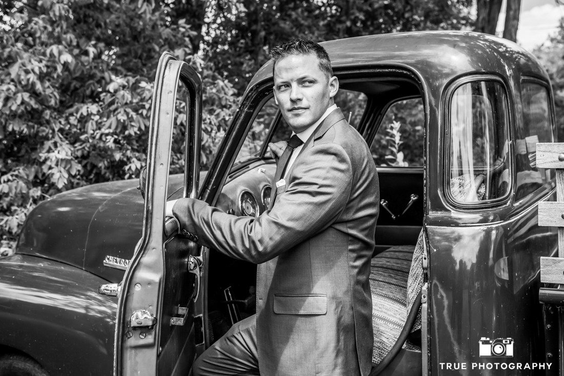 groom stepping out of classic truck