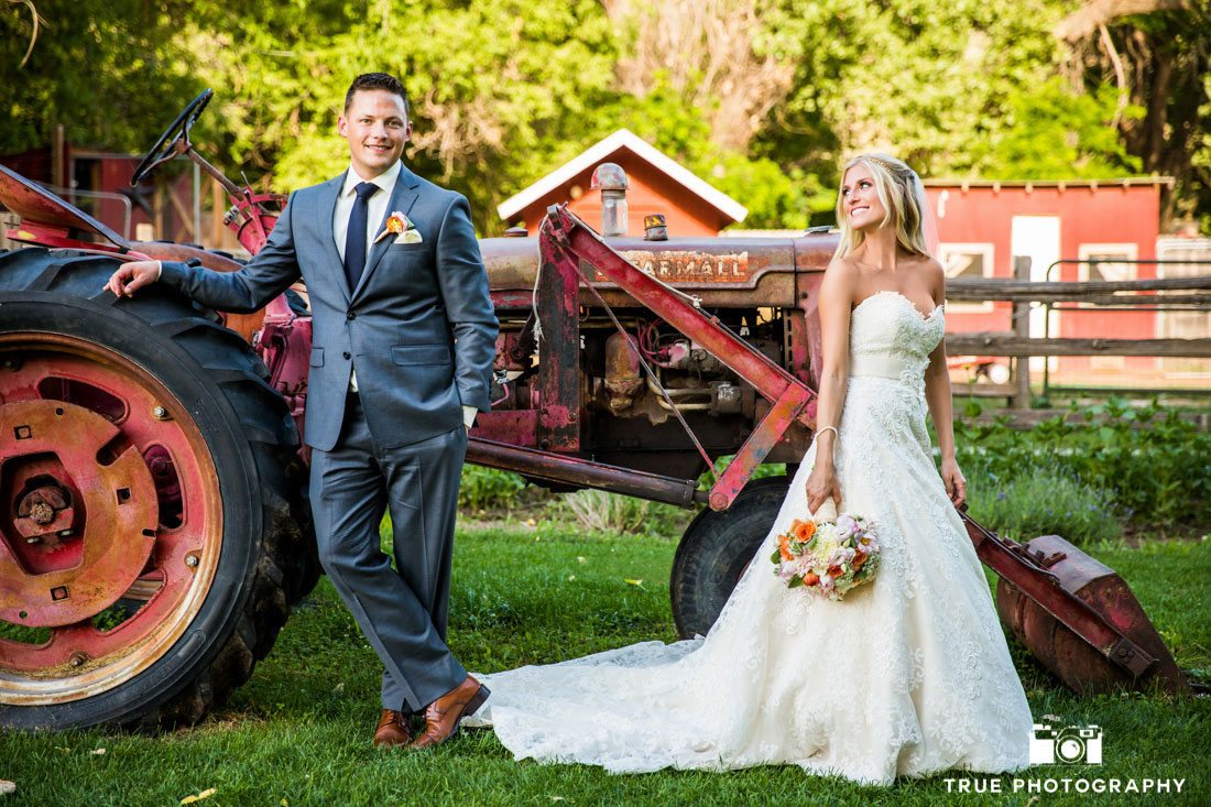 bride and groom leaning against tractor