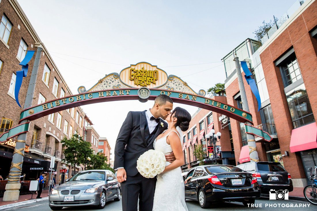 bride and groom kissing in front of gaslamp quarter sign