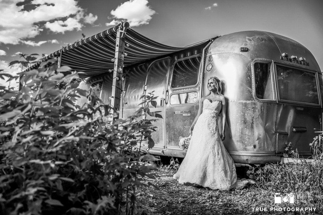 b&w photo of bride and airstream trailer