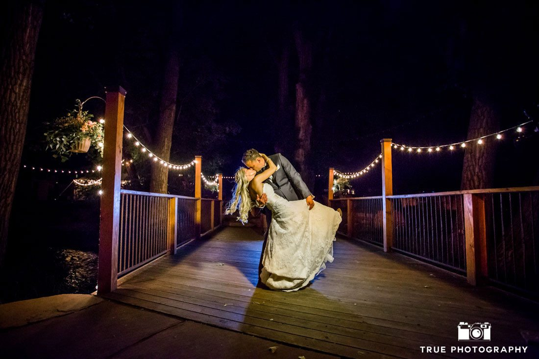 b&w groom on bridge at night
