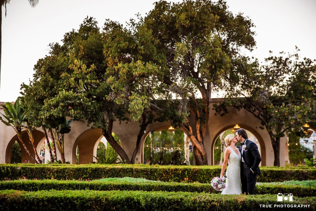 Wedding photographed of a kissing couple framed in arches at the Alcazar Garden in Balboa Park in San Diego, California.