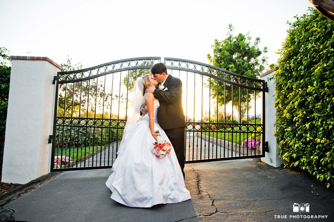 Bride and Groom Kiss in Front of Gate