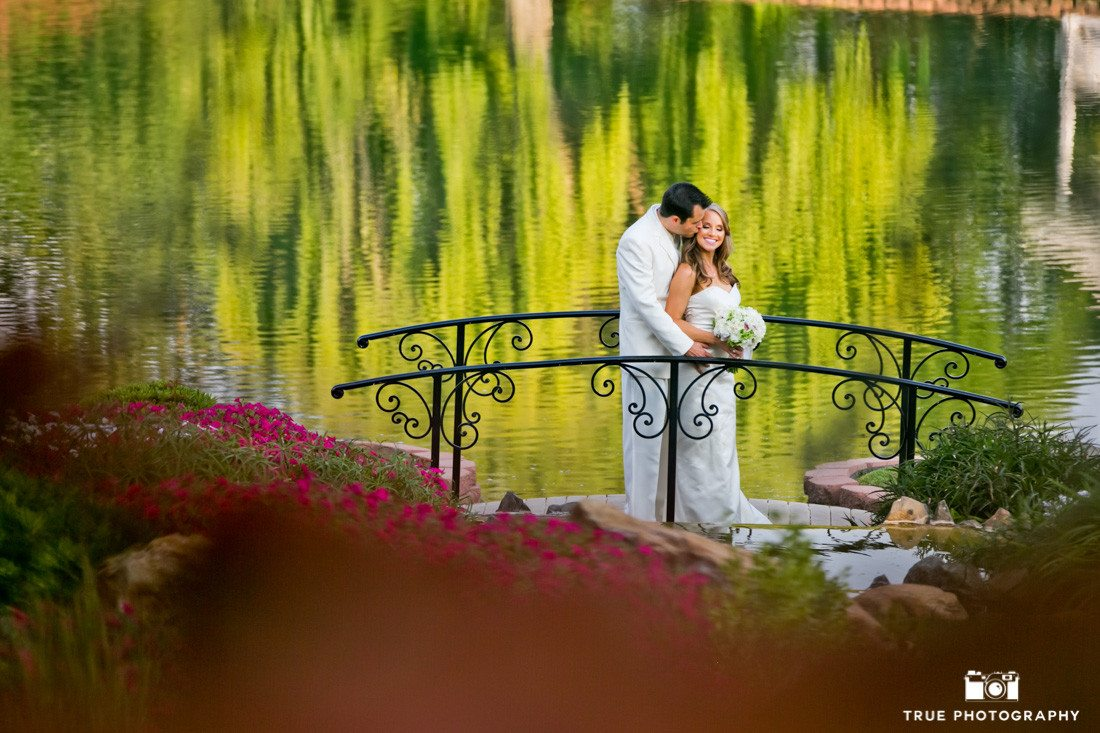 Bride and Groom pose by lake at Grand Tradition