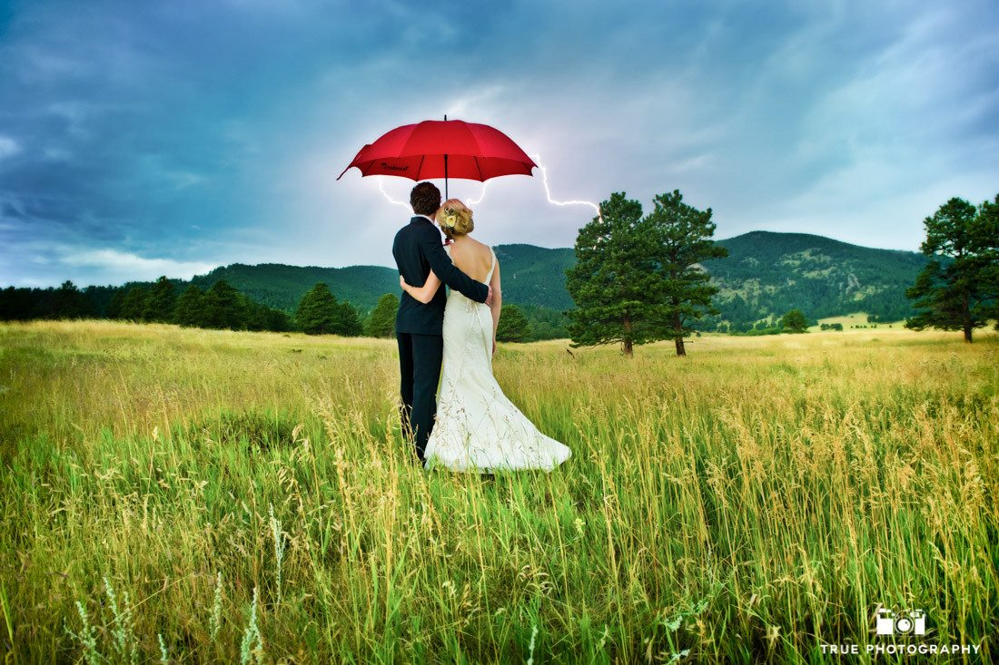 Bride and Groom standing together with red umbrella and lightning