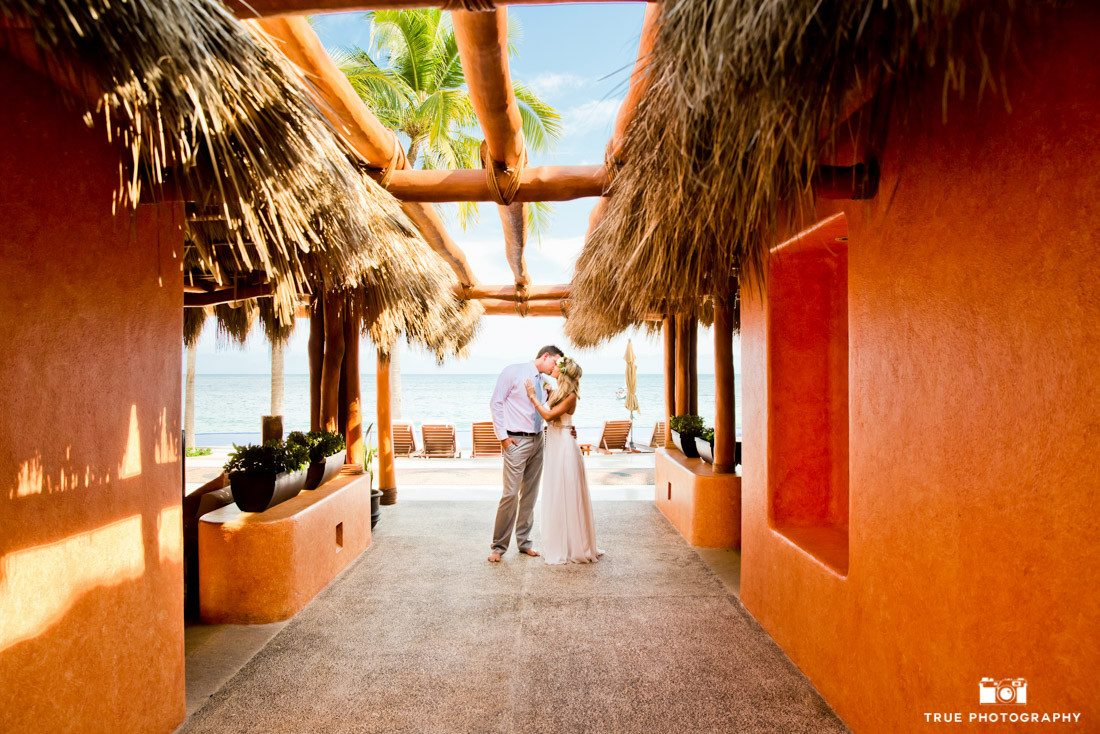 Photograph of bride and groom kissing at a destination wedding. Leading lines add emphasis to the couple.