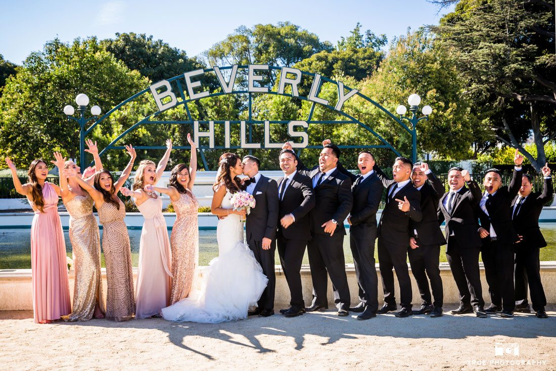Cheering wedding party in front of Beverly Hills Sign in Los Angeles, California.