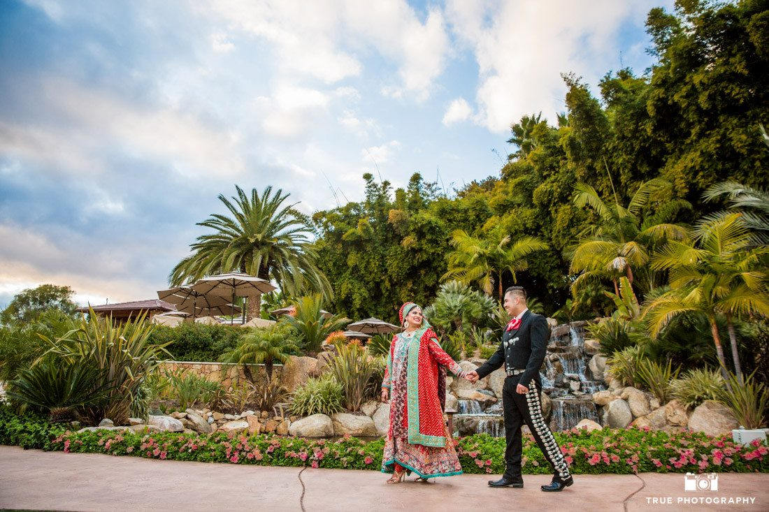 Wedding couple walking by waterfall at the Orchid Bar at the Grand Tradition Estate, Fallbrook, California.