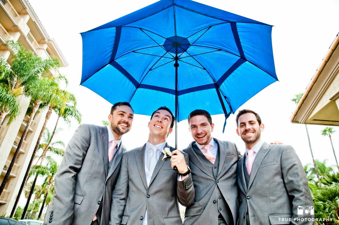 Groomsmen holding blue umbrella
