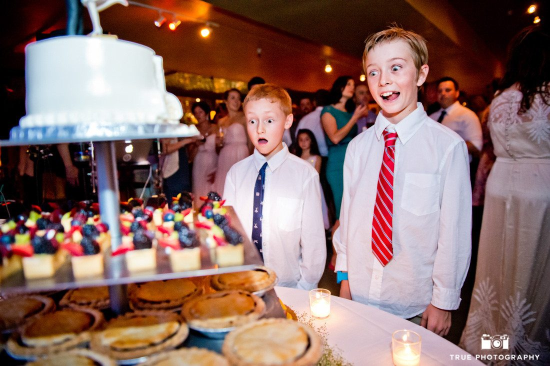 Boys making funny faces as they look at wedding cake