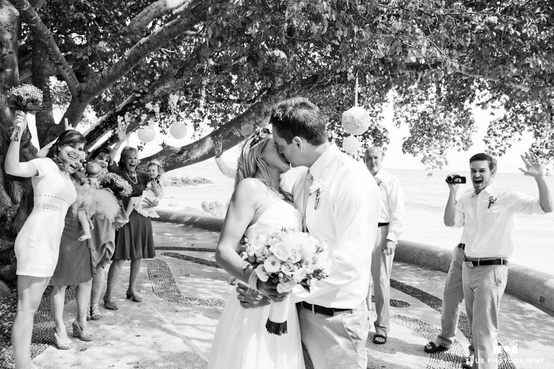 Black and white photo of couple kissing while their guests are cheering in the background.