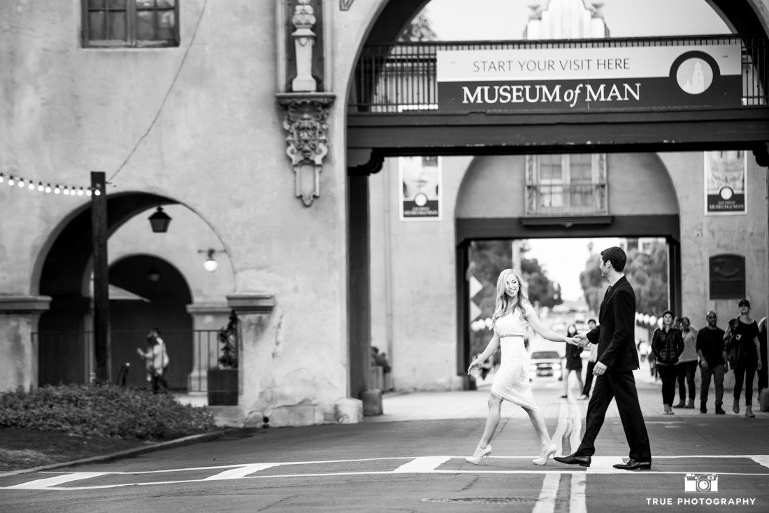 Engagement photo walking acroos a busy street at balboa Park