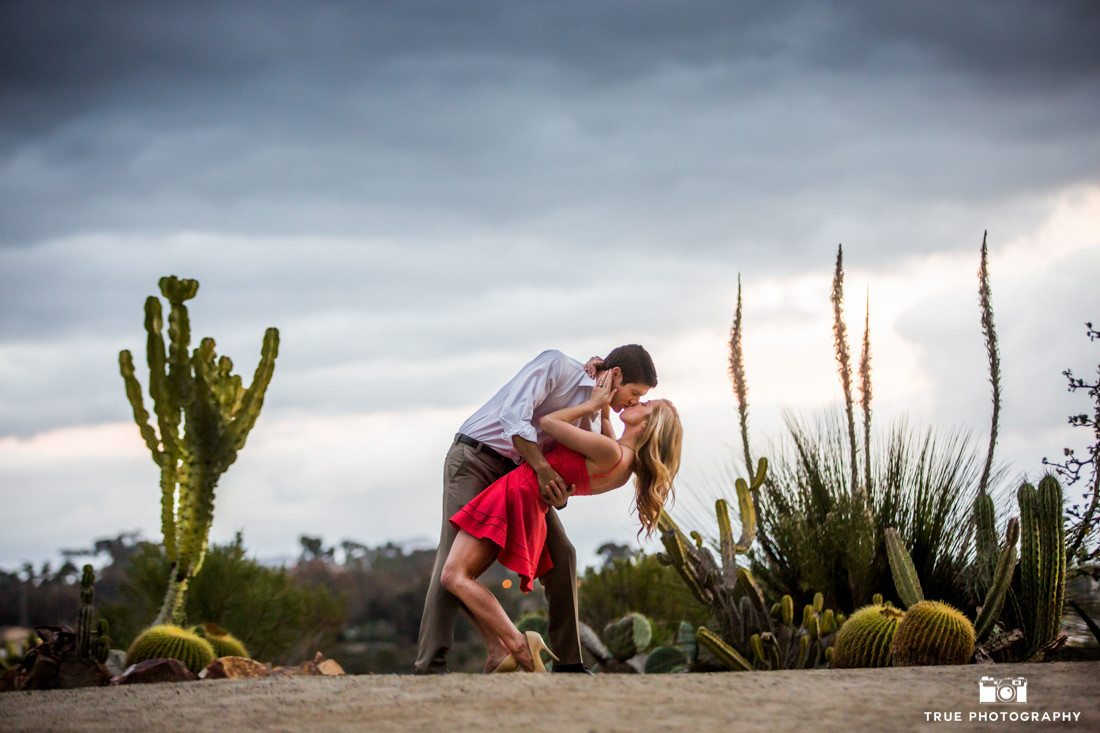 Engagement photo of a kiss and dip at Balboa Park's Desert Garden