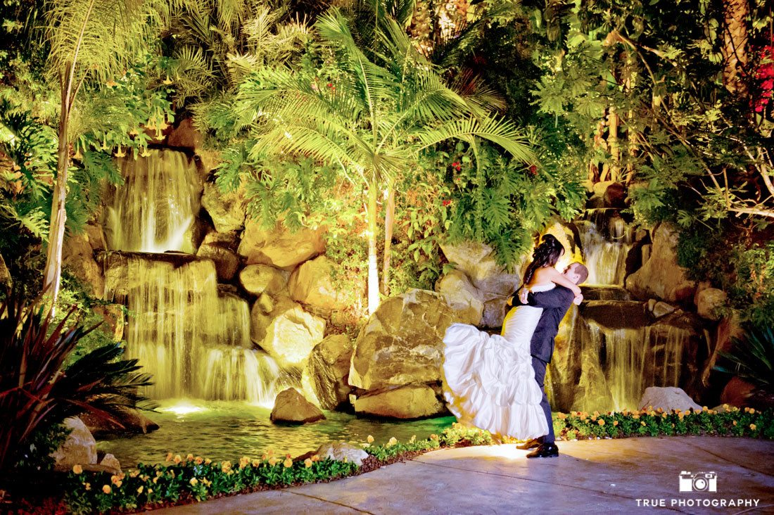 Bride and Groom kiss in front of waterfall at night