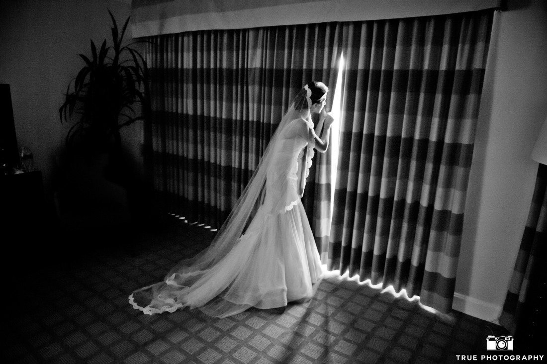 Bride waits anxiously out window before wedding ceremony