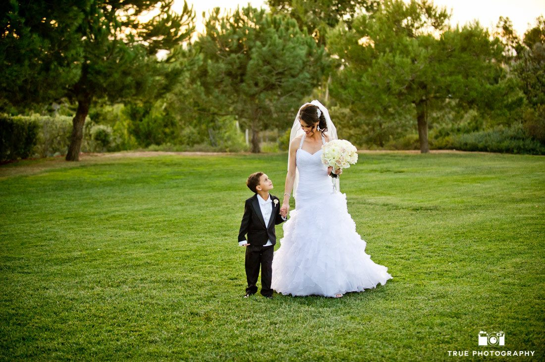 Bride walks with young boy during sunset