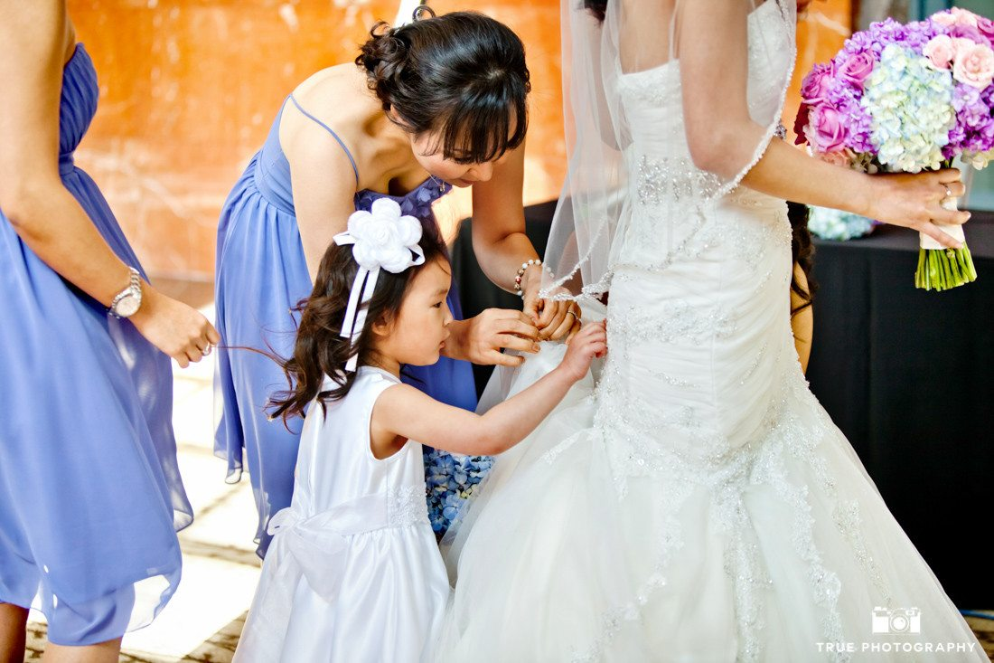 Young girl helps bride during pre-ceremony