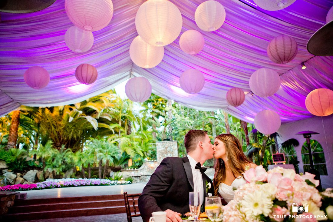 Couple kiss at sweetheart table during wedding reception