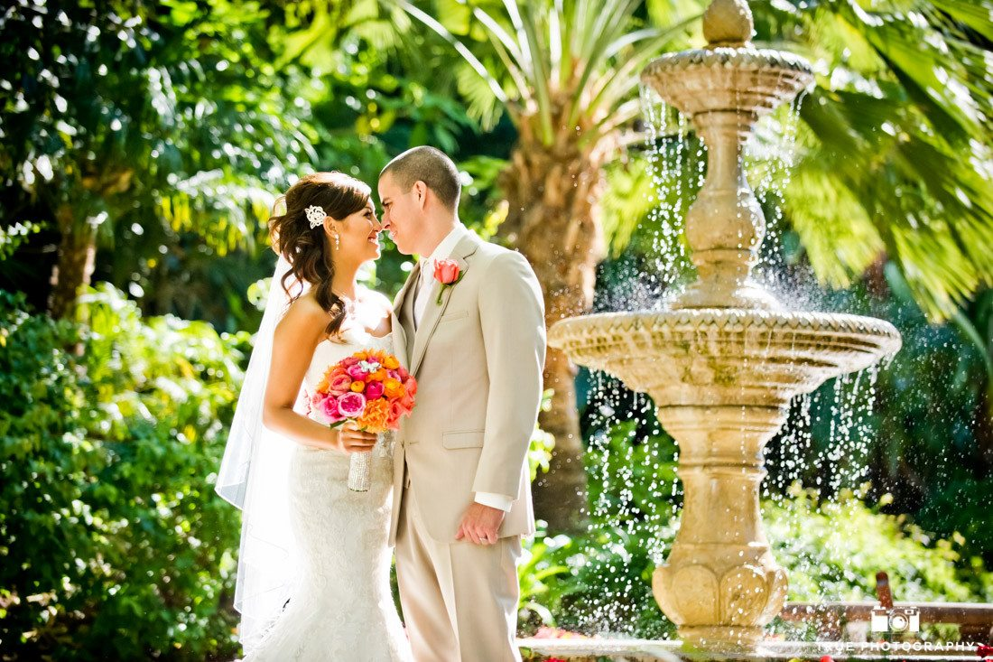 Couple lean in for kiss by flowing fountain