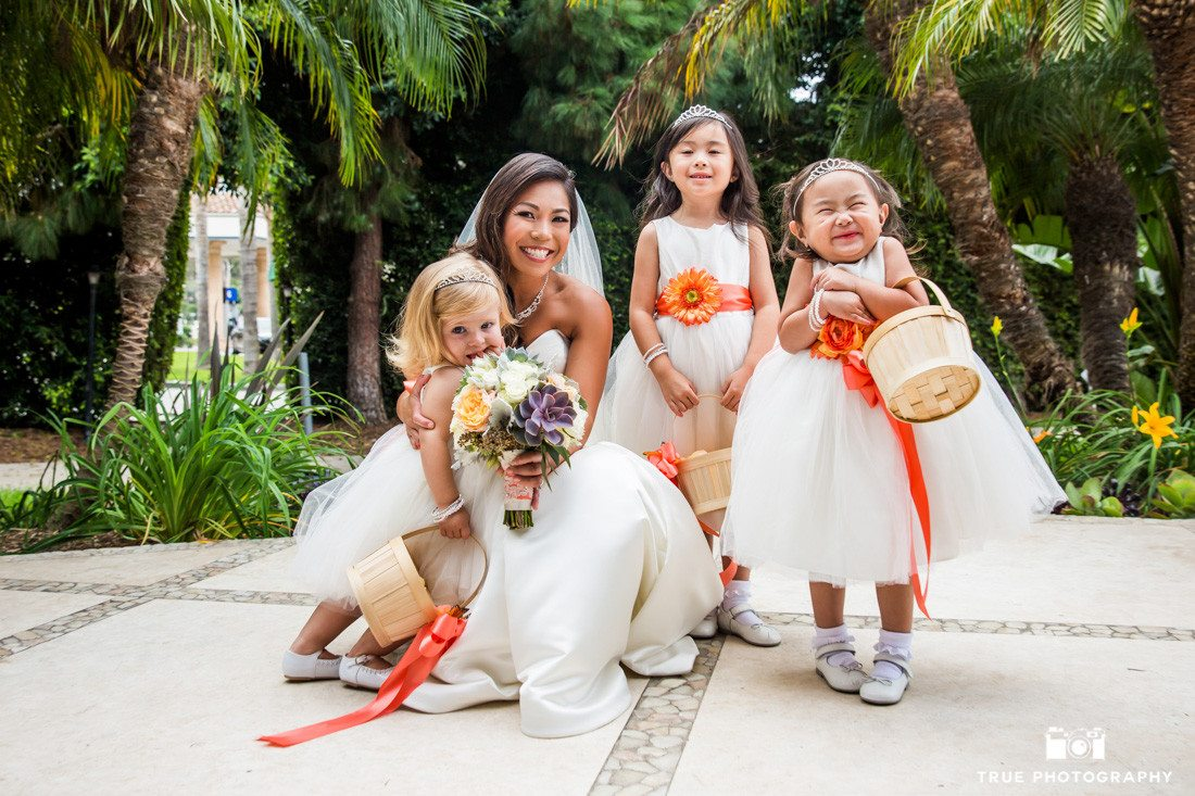 Cute Flowergirls in orange and white dresses pose with Bride