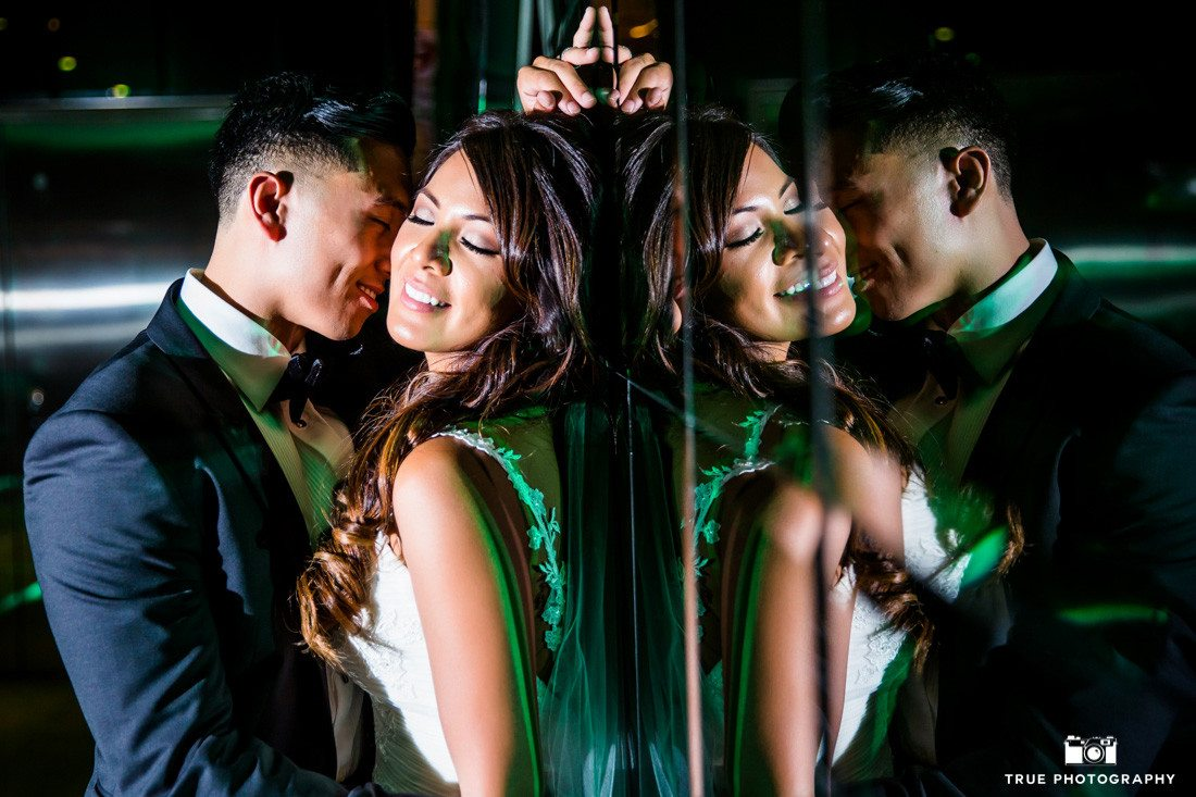 Reflective photograph of bride and groom having an intimate moment at the SLS Hotel