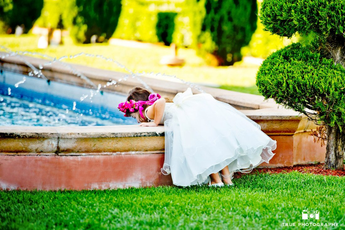 Flowergirl looks into fountain on wedding day