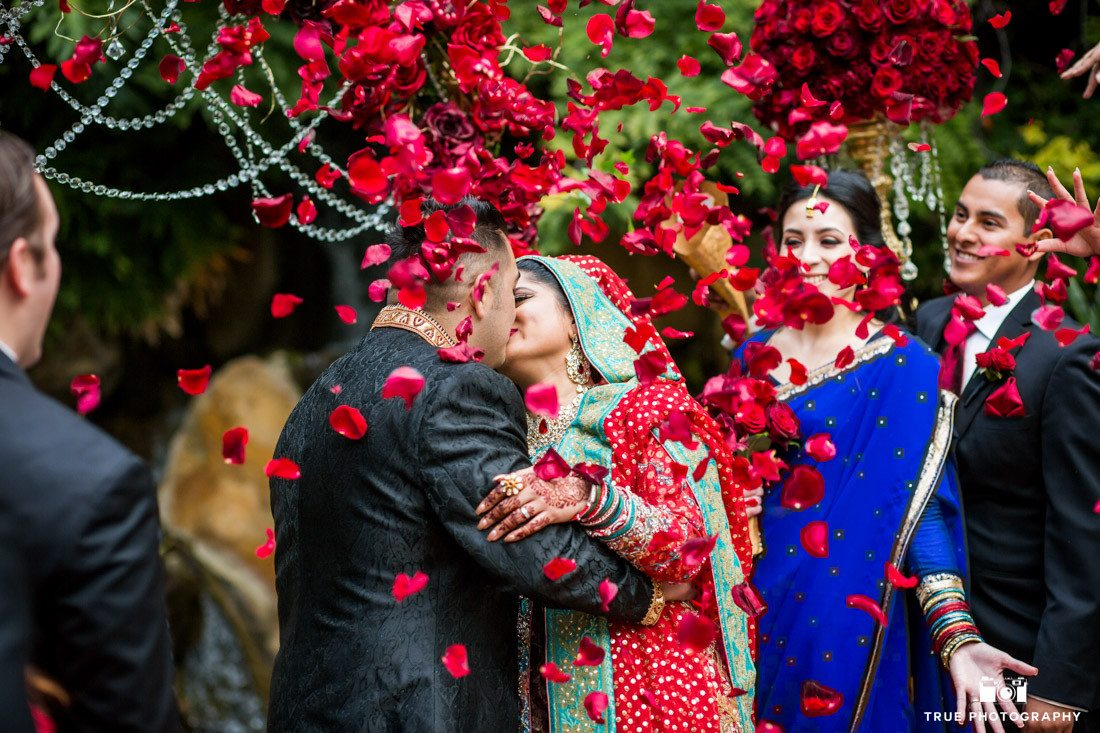 Wedding Kiss at the Grand Tradition with red rose petals flying in th air
